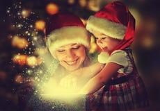 Weihnachtszaubergeschenkbox und ein glückliches Familienmutter- und -tochterbaby Lizenzfreie Stockbilder