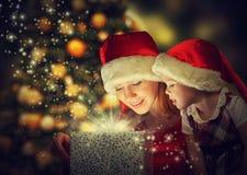 Weihnachtszaubergeschenkbox und ein glückliches Familienmutter- und -tochterbaby Stockfotos