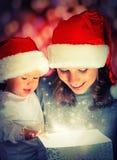 Weihnachtszaubergeschenkbox und eine glückliche Familienmutter und -baby Lizenzfreie Stockfotos