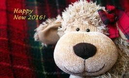 """Weihnachtszeit †""""lustiges Spielzeug-Affegesicht mit warmem rotem Plaidhintergrund Stockfotografie"""
