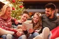 Weihnachtszeit- Familie, die lustiges Video auf digitaler Tablette aufpasst Stockfotos