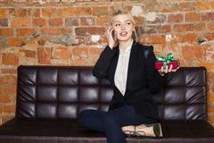 Weihnachtszeit im Büro Junge schöne blonde Geschäftsfrau auf Ledercouch Die goldene Taste oder Erreichen für den Himmel zum Eigen Stockfoto