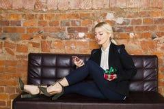 Weihnachtszeit im Büro Junge schöne blonde Geschäftsfrau auf Ledercouch Die goldene Taste oder Erreichen für den Himmel zum Eigen Lizenzfreie Stockfotografie