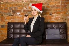 Weihnachtszeit im Büro Junge schöne blonde Geschäftsfrau auf Ledercouch Die goldene Taste oder Erreichen für den Himmel zum Eigen Stockfotos