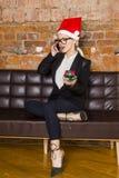 Weihnachtszeit im Büro Junge schöne blonde Geschäftsfrau auf Ledercouch Die goldene Taste oder Erreichen für den Himmel zum Eigen Stockbild