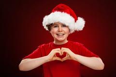 Weihnachtszeit- Junge mit Santa Claus Hat, die Herzzeichen zeigt stockfotos