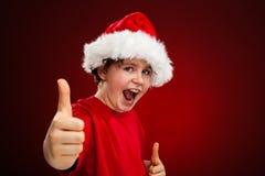 Weihnachtszeit- Junge mit Santa Claus Hat, die okayzeichen zeigt lizenzfreies stockfoto