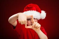 Weihnachtszeit- Junge mit Santa Claus Hat, die Zeichen zeigt stockbilder