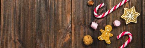 Weihnachtszuckerstangen, Lebkuchen von verschiedenen Formen, Haselnüsse, Walnüsse auf einem braunen Holztisch Kopieren Sie Platz stockfoto