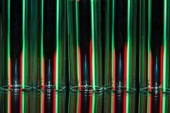 Weihnachtszusammenfassung: Vertikale Streifen des roten und grünen Lichtes, das einen Feiertags-Hintergrund bildet Lizenzfreie Stockfotografie