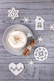 Weihnachtszusammensetzung auf einem grauen Hintergrund Kaffeecappuccino mit Zimt- und Weihnachtsbaumdekorationen Beschneidungspfa Lizenzfreies Stockfoto