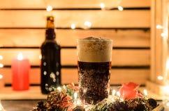 Weihnachtszusammensetzung mit einem Becher dunklem Bier stockbild