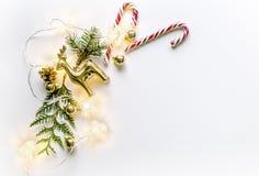 Weihnachtszusammensetzung mit einem Rotwild, Tannenzweigen, Kegeln und Bällen des neuen Jahres, Eiskristallen und einem Hering Lizenzfreies Stockfoto
