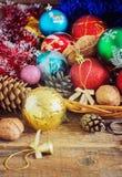 Weihnachtszusammensetzung mit Geschenken Korb, rote Bälle, Kiefernkegel, Schneeflocken auf Holztisch Abbildung der roten Lilie Lizenzfreie Stockfotografie