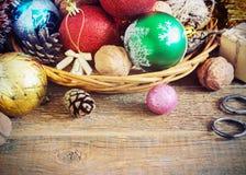 Weihnachtszusammensetzung mit Geschenken Korb, rote Bälle, Kiefernkegel, Schneeflocken auf Holztisch Abbildung der roten Lilie Stockfoto