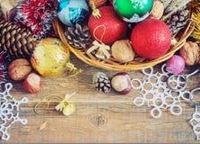 Weihnachtszusammensetzung mit Geschenken Korb, rote Bälle, Kiefernkegel, Schneeflocken auf Holztisch Abbildung der roten Lilie Stockfotografie