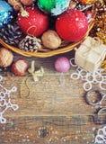 Weihnachtszusammensetzung mit Geschenken Korb, rote Bälle, Kiefernkegel, Schneeflocken auf Holztisch Abbildung der roten Lilie Stockbild