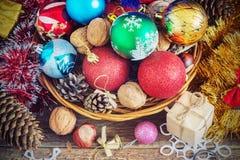 Weihnachtszusammensetzung mit Geschenken Korb, rote Bälle, Kiefernkegel, Schneeflocken auf Holztisch Abbildung der roten Lilie Lizenzfreie Stockbilder