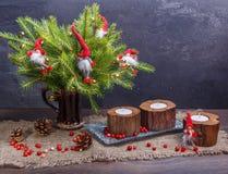 Weihnachtszusammensetzung mit Geschenken und brennender Kerze Korb, rote Bälle, Kiefernkegel, Schneeflocken auf Grey Background Lizenzfreies Stockfoto