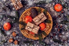 Weihnachtszusammensetzung mit Tangerinen, Geschenkboxen, Kegel Stockfotos