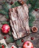 Weihnachtszusammensetzung mit Weihnachtsgeschenken, Barkenbeschaffenheit, Granatapfel, Tannenzweige auf hölzernem Hintergrund stockfotos