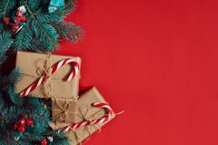 Weihnachtszusammensetzung von Kiefernkegeln, -Fichtenzweigen und -stapel Geschenkboxen auf rotem Hintergrund Lizenzfreies Stockbild