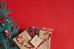 Weihnachtszusammensetzung von Kiefernkegeln, -Fichtenzweigen und -stapel Geschenkboxen auf rotem Hintergrund Stockbild