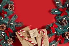 Weihnachtszusammensetzung von Kiefernkegeln, -Fichtenzweigen und -stapel Geschenkboxen auf rotem Hintergrund Stockfotos