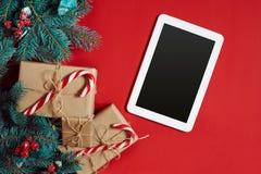 Weihnachtszusammensetzung von Kiefernkegeln, -Fichtenzweigen und -stapel Geschenkboxen auf rotem Hintergrund Lizenzfreie Stockfotos