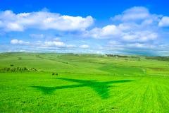 Weilanden, hemel en wolken en een vliegtuigschaduw over gras Stock Afbeelding