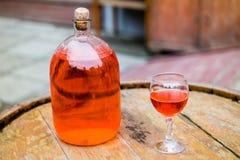 Wein in der alten Flasche auf einem Fass Lizenzfreie Stockfotografie