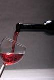 Wein, der aus einer Flasche gegossen wird. Stockfotos
