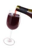 Wein fließt in Weinglas Stockbild