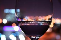 Wein-Glas mit unscharfen Leuchten Stockbild