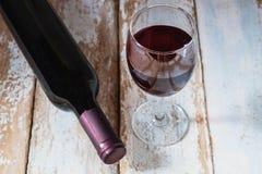 Wein-Glas und Wein-Flasche auf altem hölzernem Hintergrund lizenzfreie stockbilder