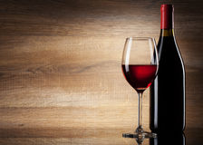 Wein-Glas und Flasche auf einem hölzernen Hintergrund Lizenzfreie Stockfotos