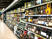 Wein legt mit Preisen auf Anzeige am Speicher in Kharkov, Uktaine beiseite Defocused Reihen von Wein-Alkoholflaschen auf Th stockfotografie