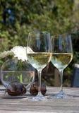Wein, Sonnenbrillen u. Blumen auf hölzerner Patiotabelle Stockbild