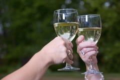 Wein-Toast-Gläser und Chardonnay draußen Stockfotografie