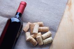 Wein und Korken auf Holztisch Stockfotografie