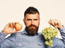 Weinbauer mit ernstem Gesicht hält Trauben und rote Frucht Lizenzfreie Stockfotos