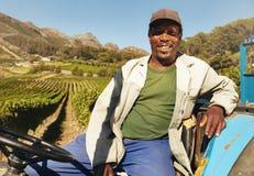 Weinbergsarbeiter, der auf seinem Traktorlächeln sitzt Stockfotografie