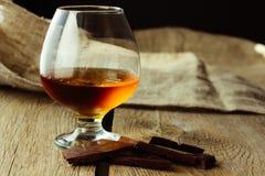 Weinbrandglas und -schokolade Stockbild