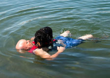 Weiner dog raft. Man with a dachshund dog on his chest floating in the river Royalty Free Stock Photo