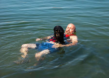 Weiner dog raft. Man with a dachshund dog on his chest floating in the river Stock Photos