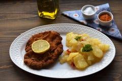 Weiner schnitzel με τη σαλάτα πατατών σε ένα ξύλινο υπόβαθρο στοκ φωτογραφία