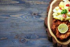 Weiner schnitzel με τη σαλάτα πατατών σε ένα ξύλινο υπόβαθρο στοκ φωτογραφίες με δικαίωμα ελεύθερης χρήσης