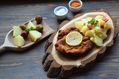 Weiner schnitzel με τη σαλάτα πατατών σε ένα ξύλινο υπόβαθρο στοκ εικόνες