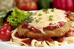 Weiner Schnitzel. Topped with a rich tomato sauce and melting cheese, over ribbon pasta stock photos