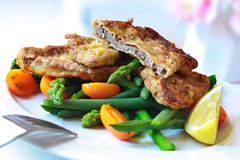 Weiner Schnitzel. Delicious Weiner Schnitzel, with asparagus, green beans, and orange cherry tomatoes royalty free stock photography